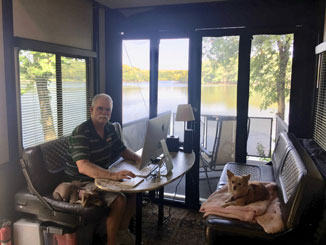Ron sitting in office by a lake